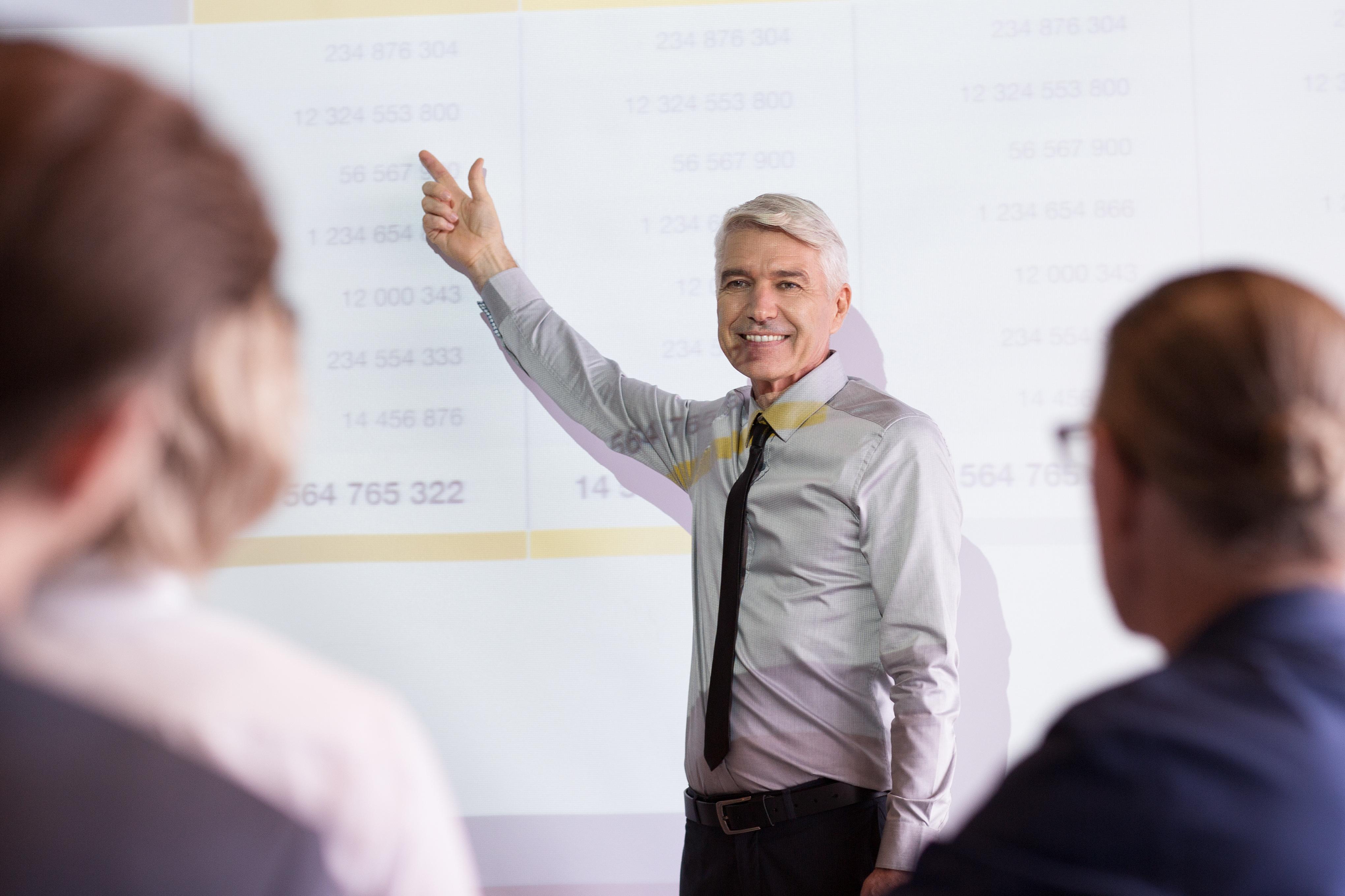 Smiling Senior Lecturer Coaching Business Team